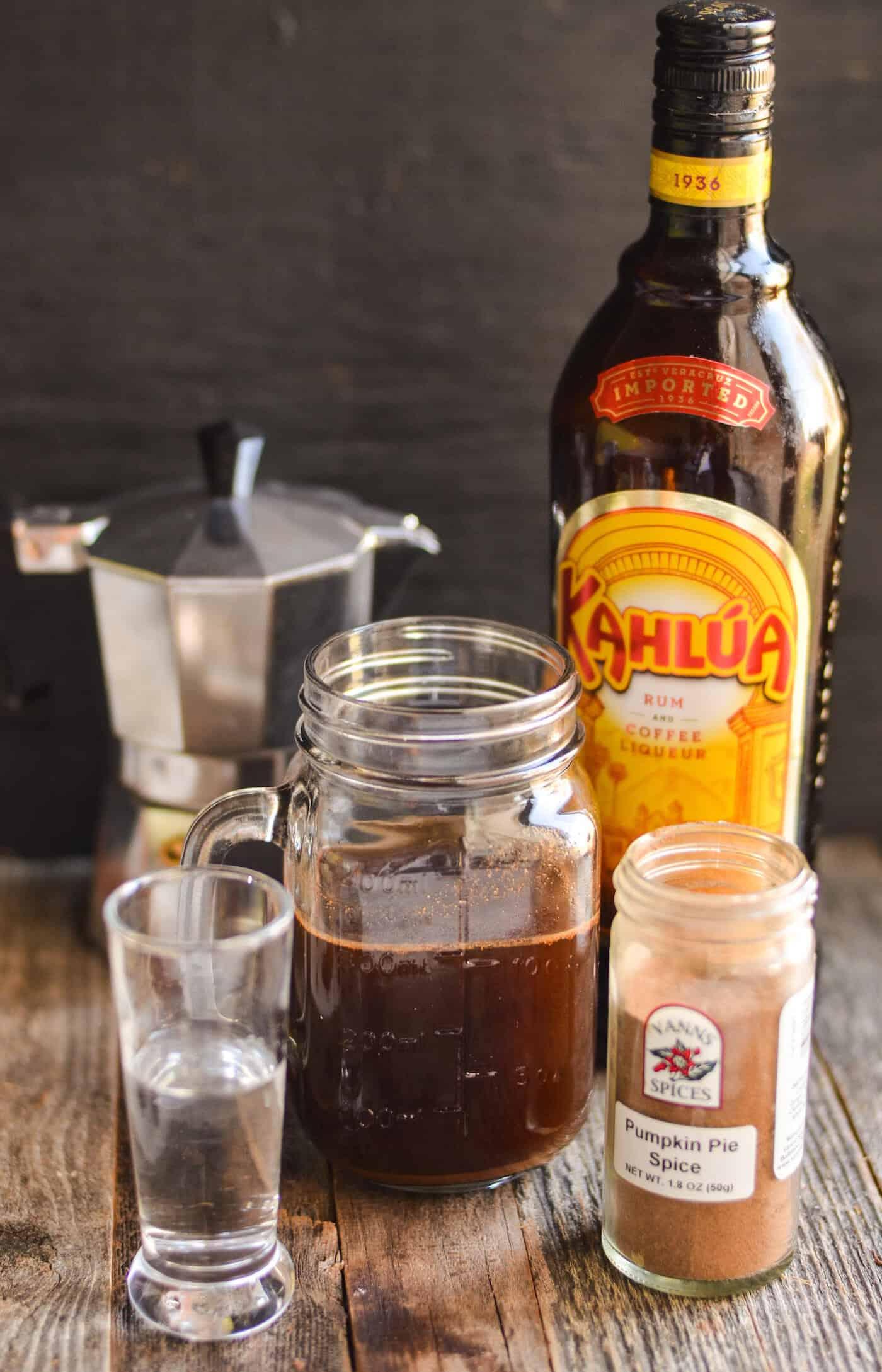 Coffee in a mason jar, bottle of Kahlua, pumpkin pie spice, shot of vodka