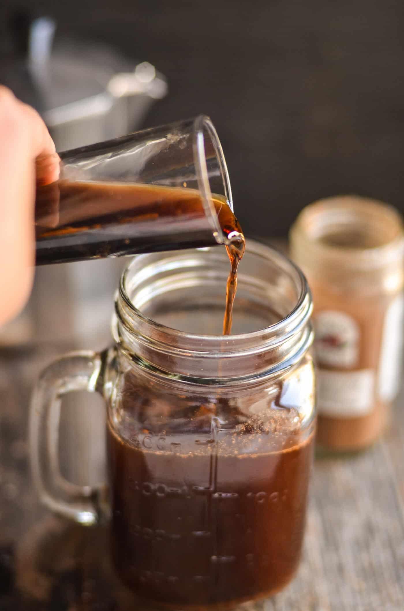 Pouring Kahlua into a mason jar glass mug
