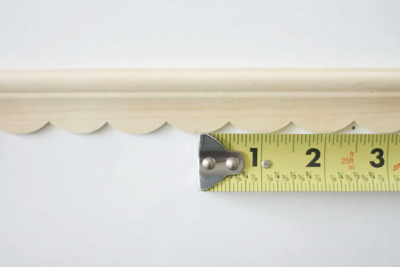 Measuring tape next to a piece of wood trim