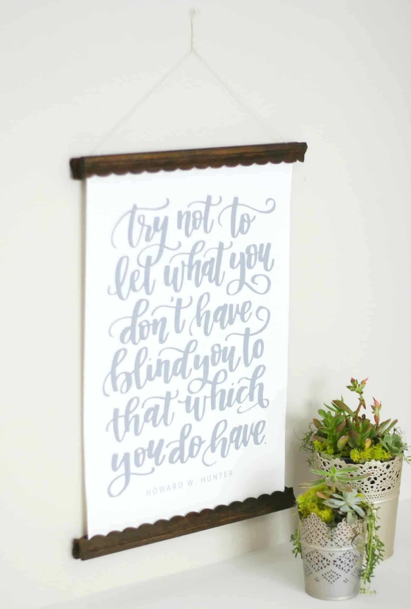Use scalloped wood trim and magnets to make the most budget friendly poster hanger ever! Get any trim you like and your favorite stain color to customize.
