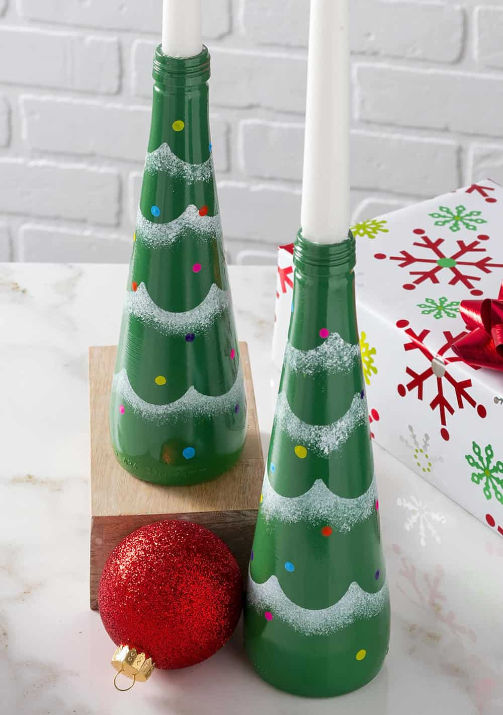 Recycle glass soda bottles into these fun and modern Christmas candle holders made to look like trees! SO easy to make and customize.