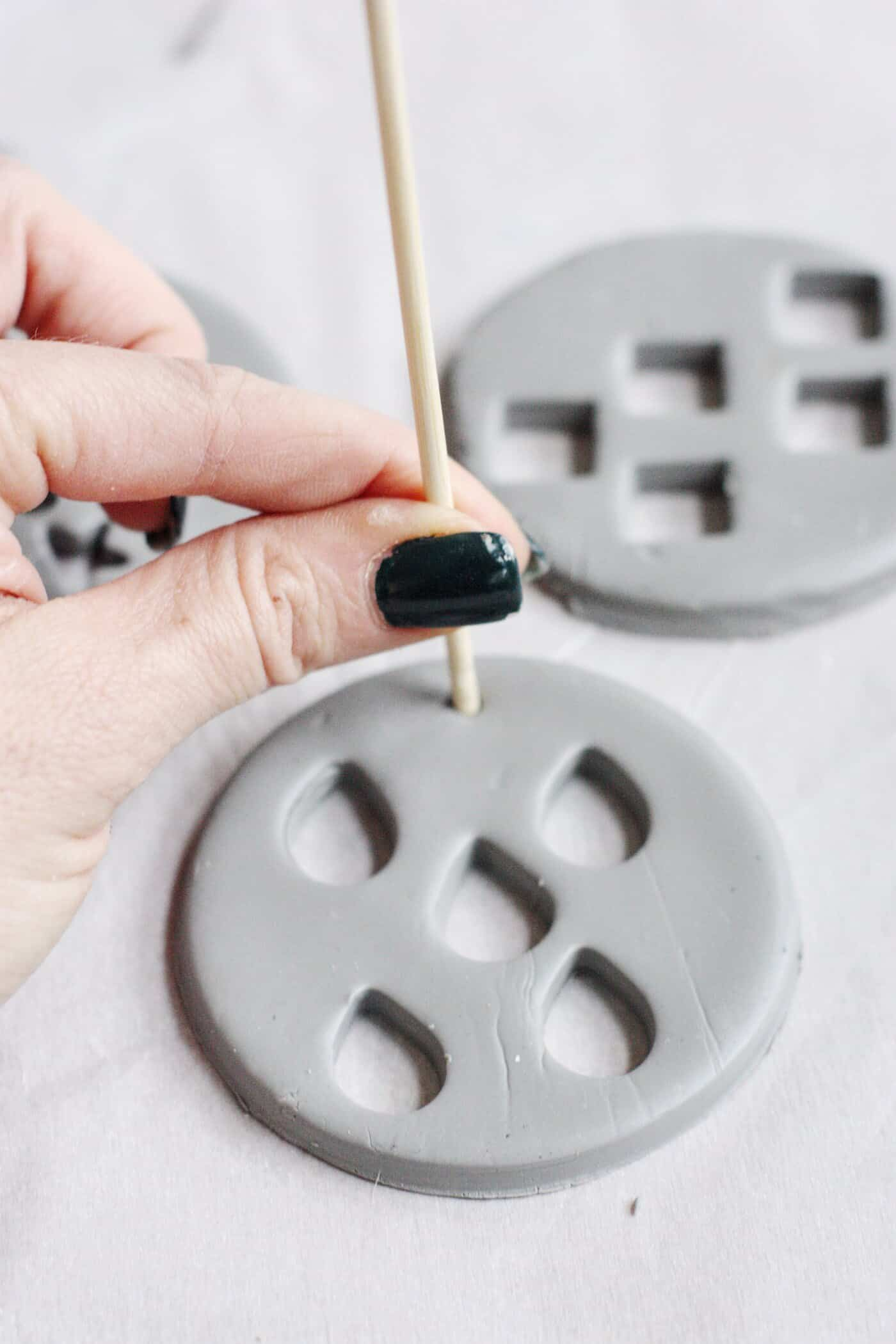 Press a hole into the top of a clay ornament using a skewer