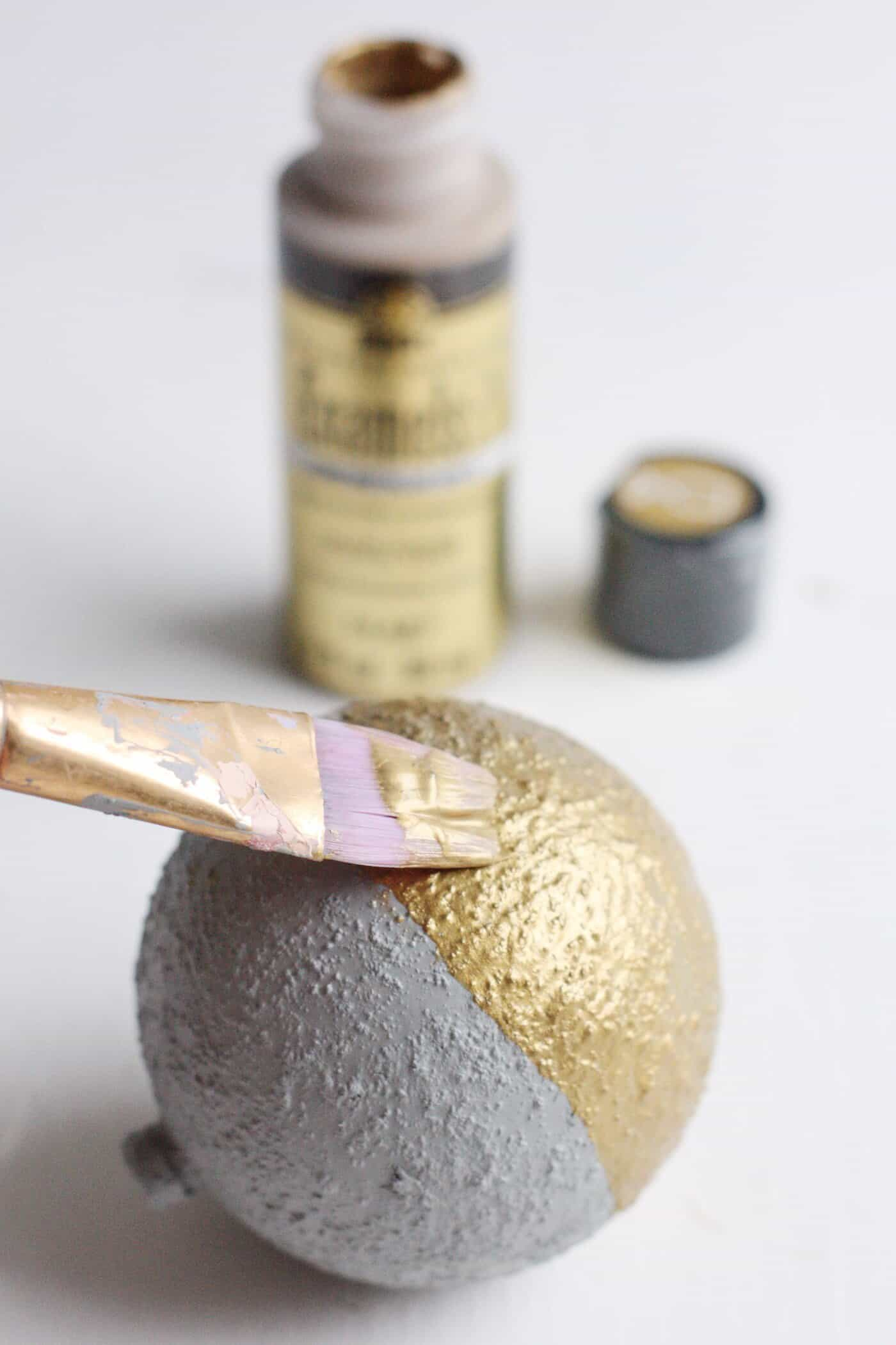 Painting the bottom half of a cement ornament with metallic gold paint