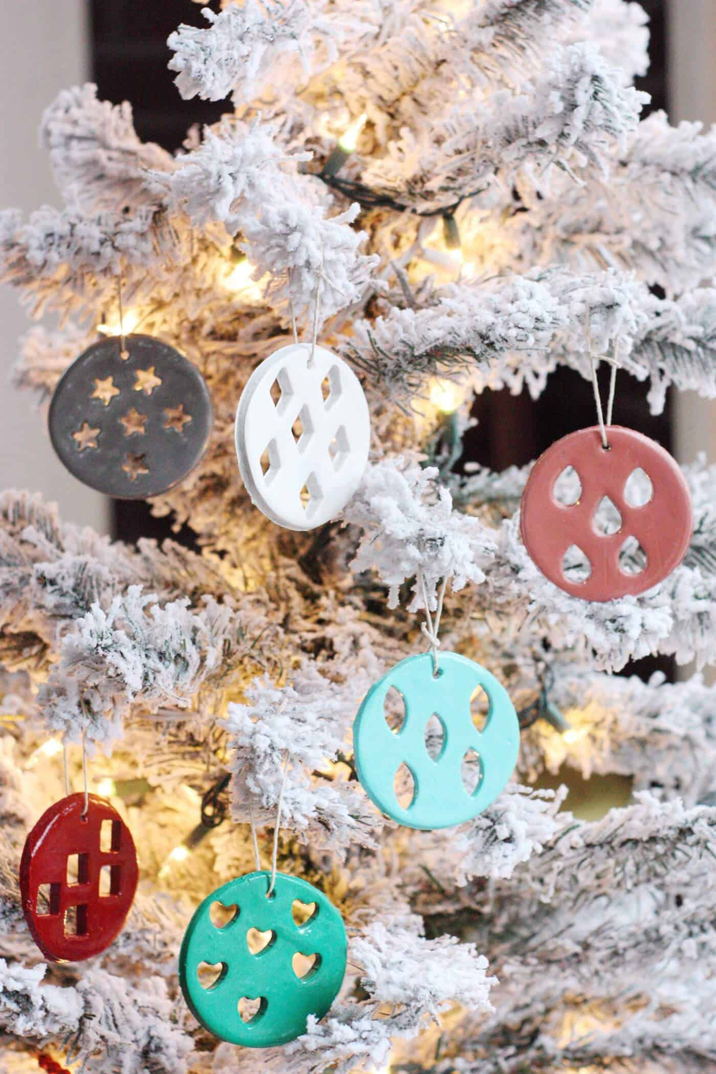 DIY clay Christmas ornaments hanging from a frosted tree
