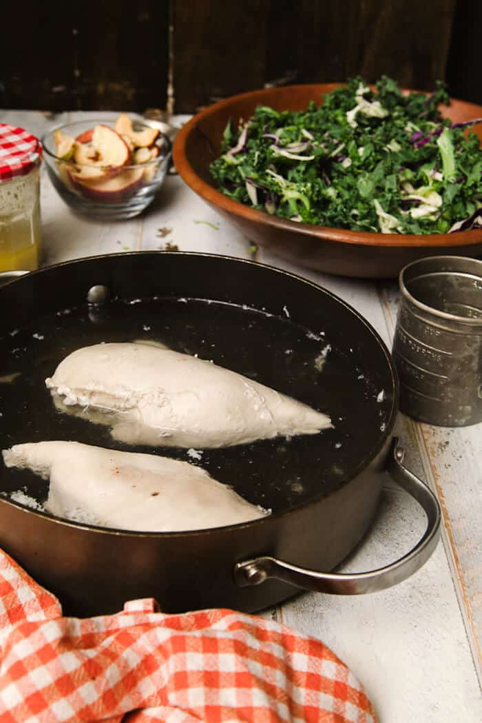 Boiled chicken breasts sitting in water in a pan