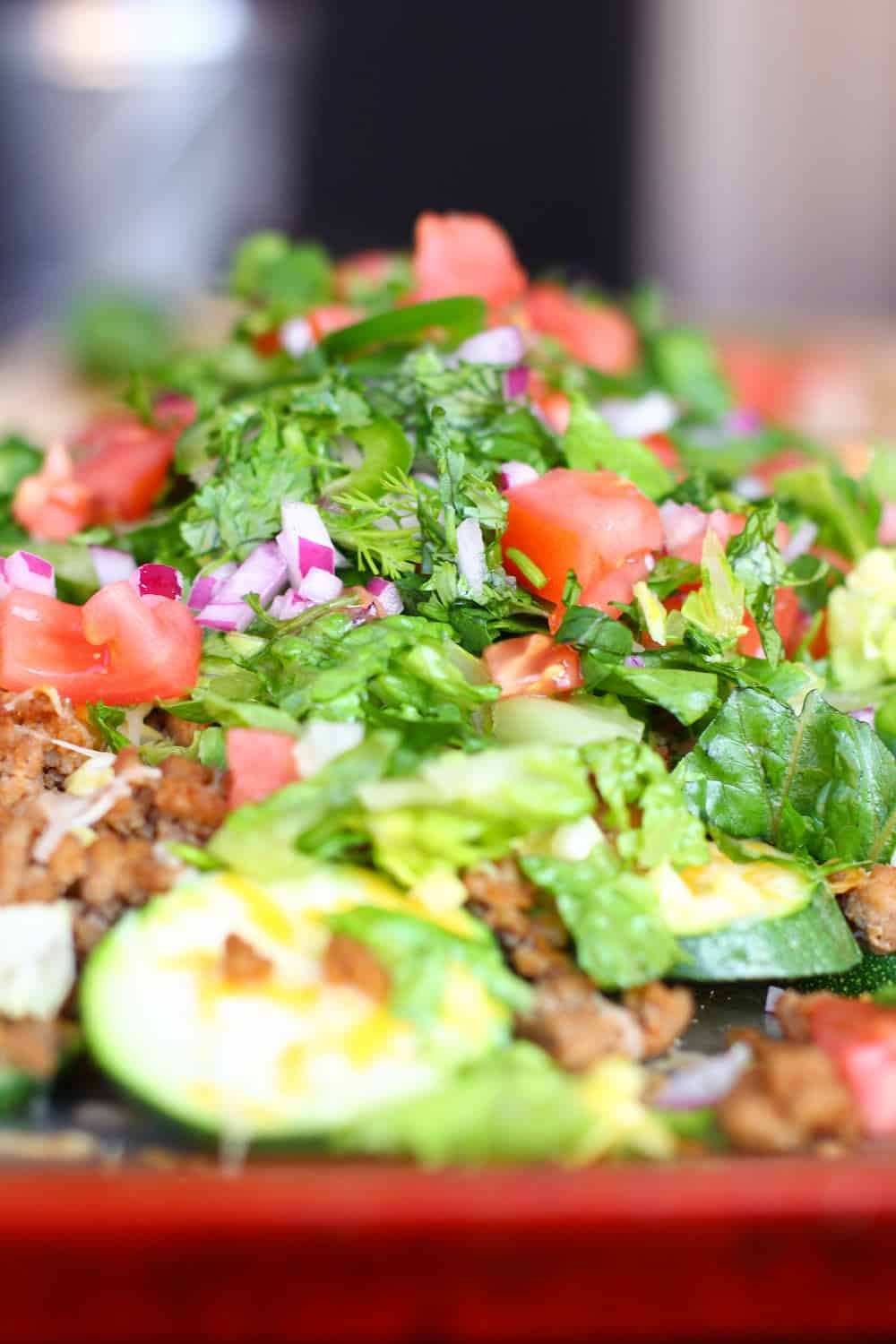 Pile of zucchini nachos with fake meat crumbles, tomato, onion, and lettuce