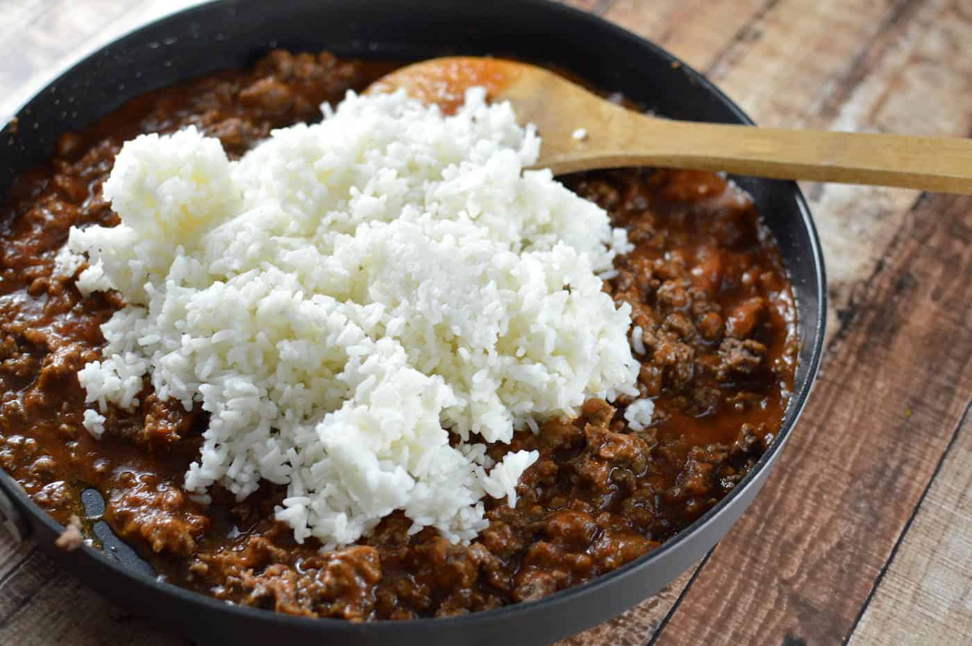 Adding rice to a pan of ground beef