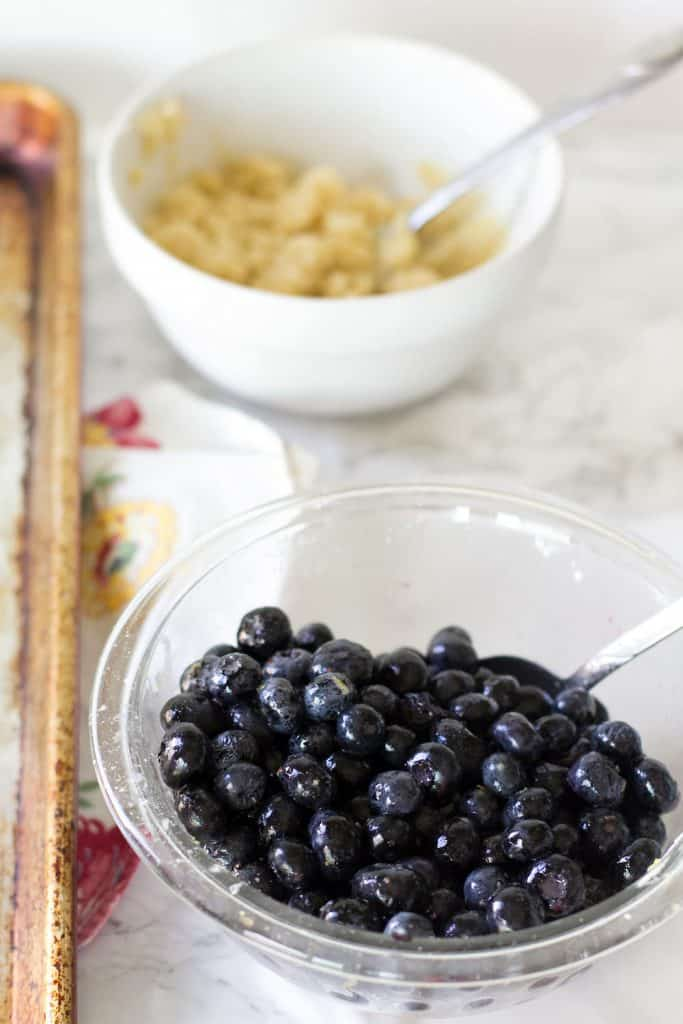 Blueberries in a glass bowl mixed with lemon juice and lemon zest