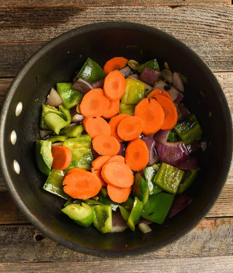 cooking carrots, pepper, and onion in a pan
