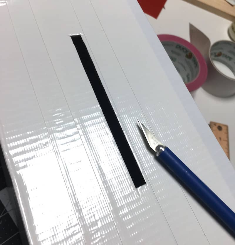 Cut a slit in the top of the shoebox with an X-Acto craft knife