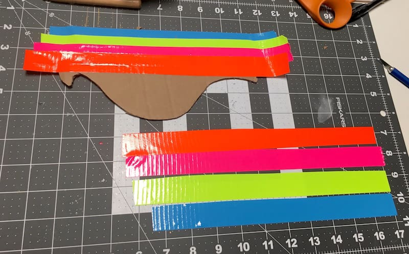 Cover the cardboard pieces with orange, pink, neon yellow, and blue Duck Tape