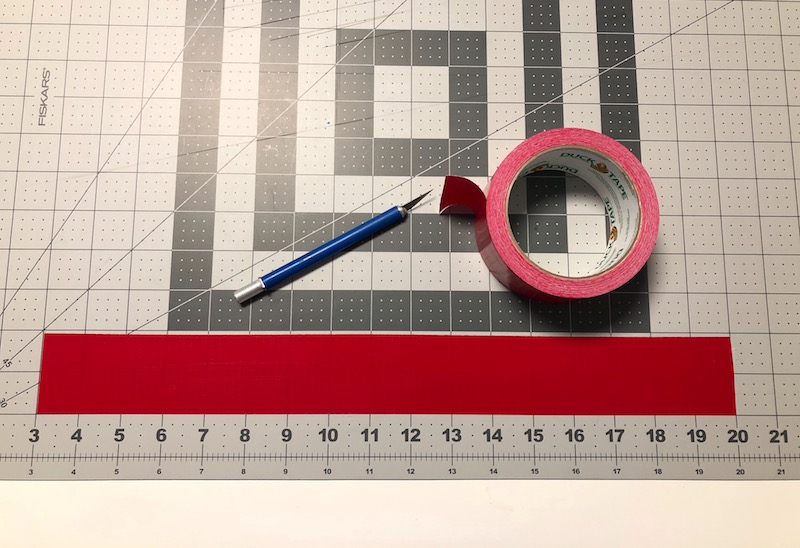 Place a piece of Duck Tape on a cutting mat