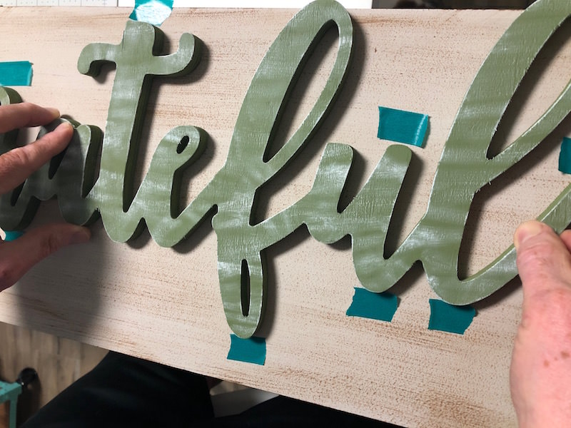 Glue down a wood word onto a plaque