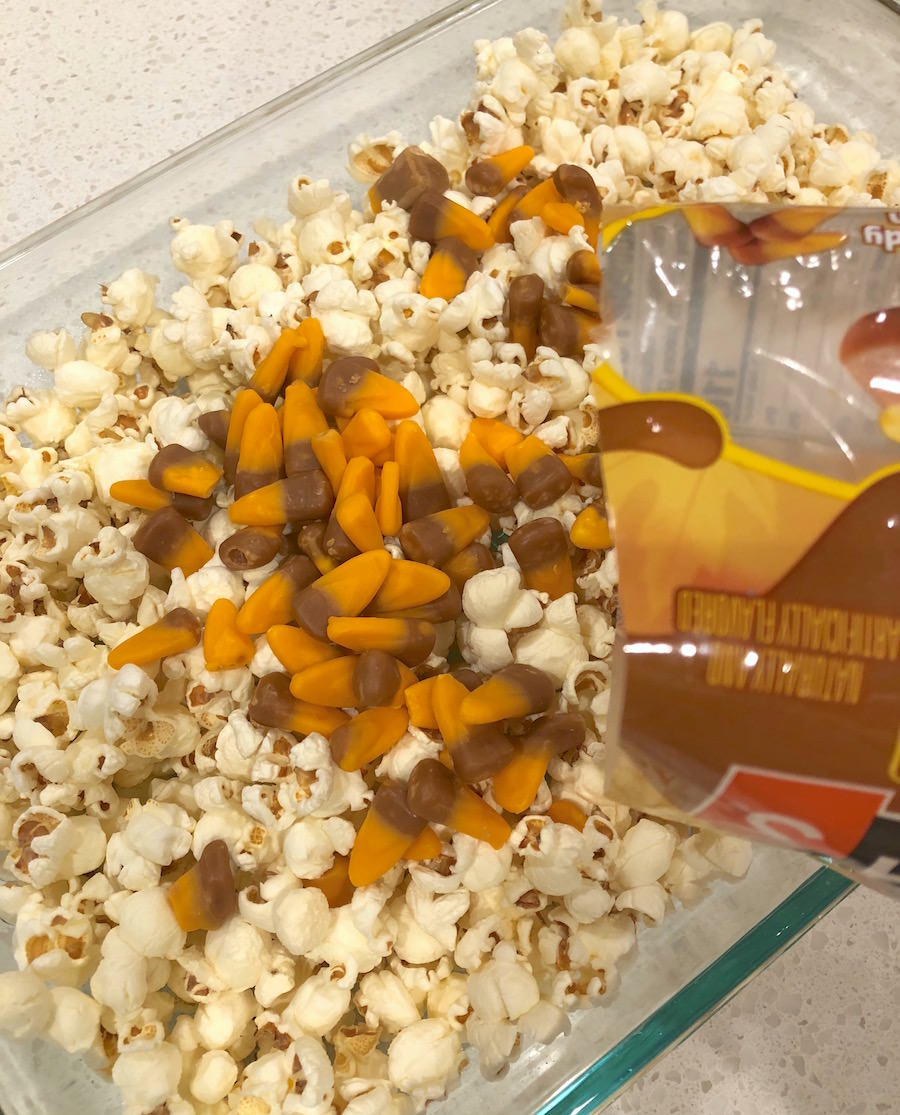 Pour candy corn into the popcorn