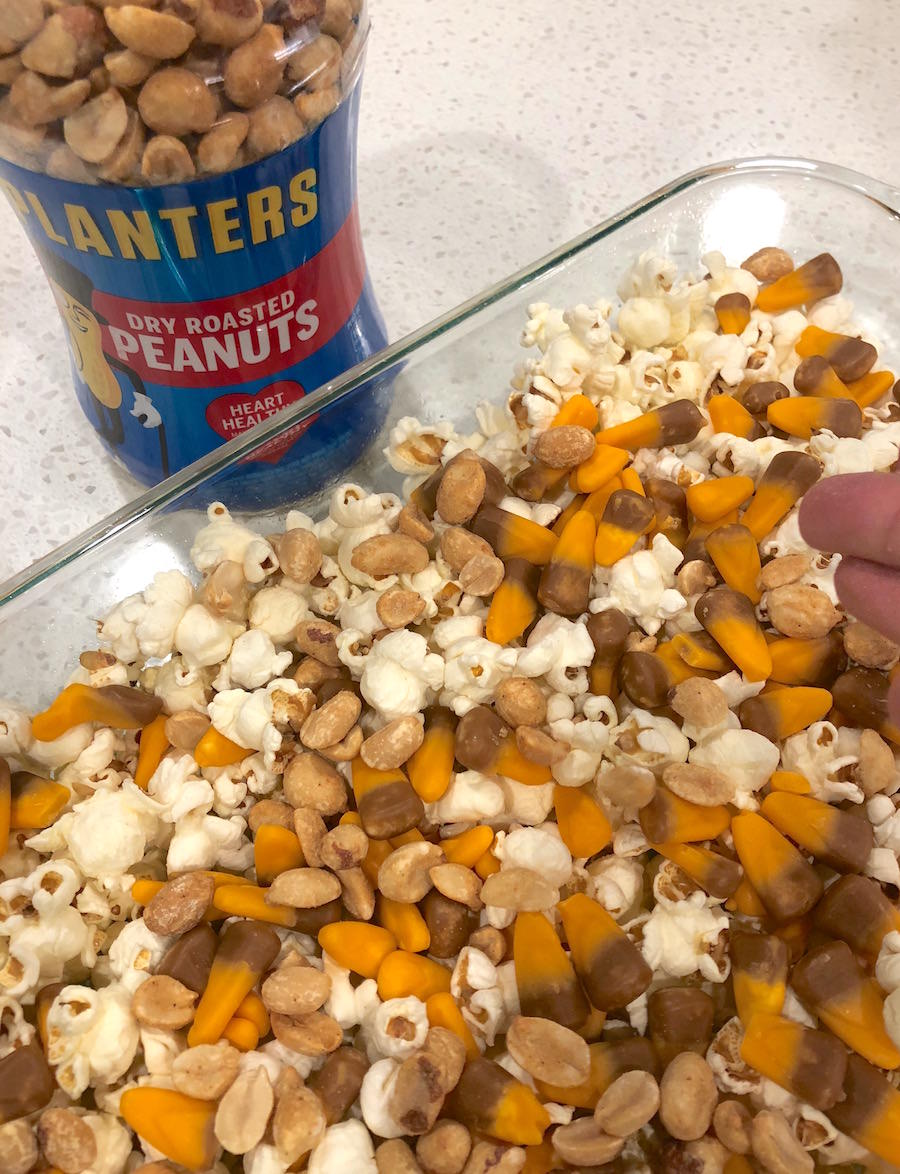 Pour peanuts on top of the popcorn