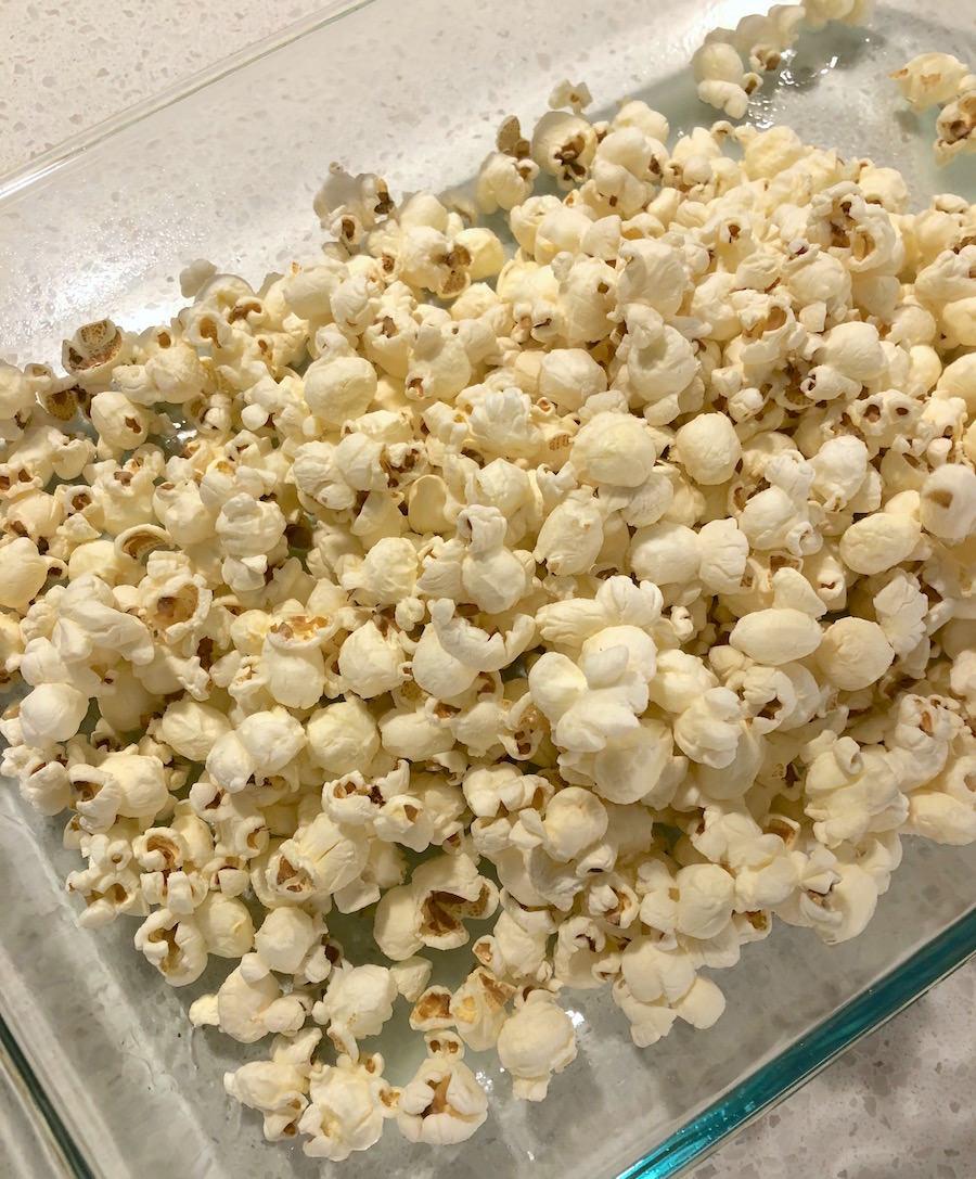 Pour popcorn into a glass casserole dish