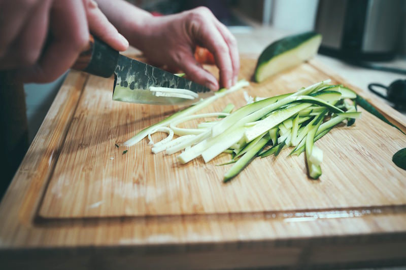 Chopping zucchini on a wood cutting board