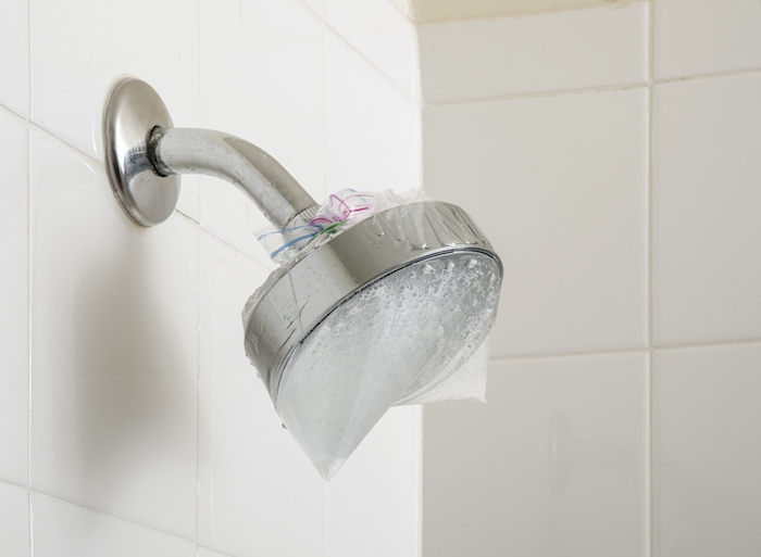 home cleaning tips - Showerhead soaking in water and vinegar in a plastic bag
