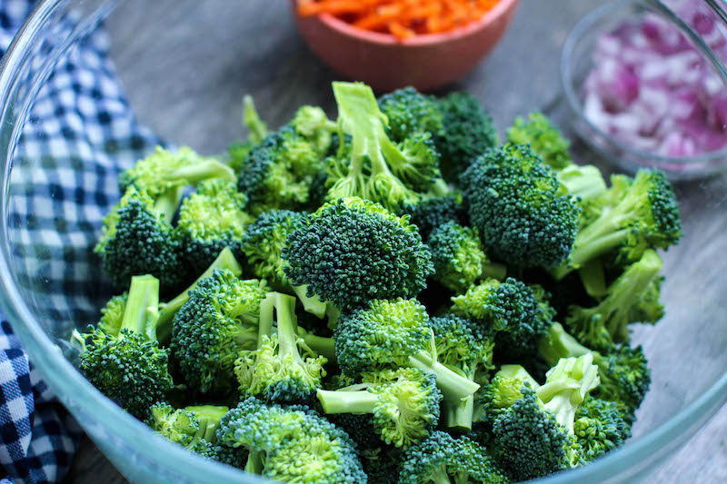 Fresh broccoli sitting in a clear glass bowl with shredded carrot and chopped onion in the background