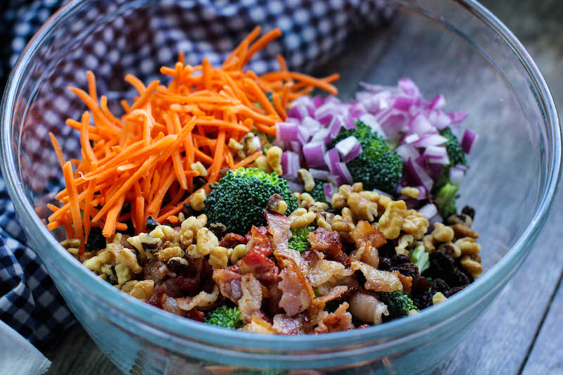 ingredients for a broccoli salad - shredded carrot, broccoli, red onion, bacon, etc
