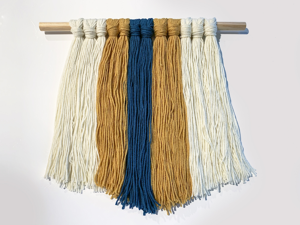 DIY yarn wall hanging laying on a white background
