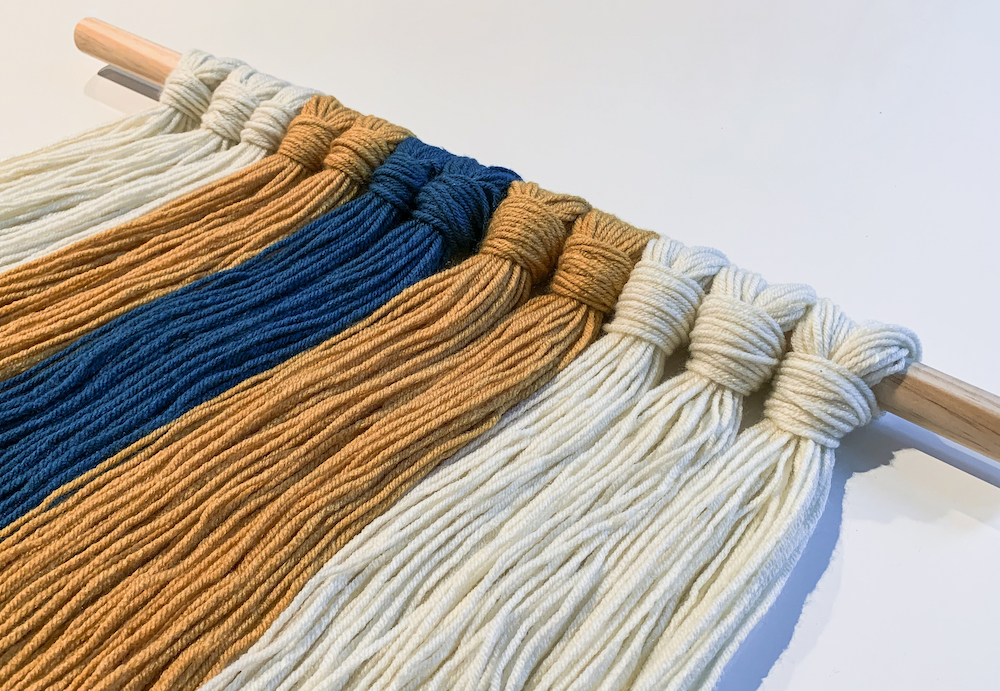teal mustard and white yarn attached to a dowel rod
