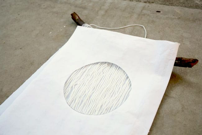 A circle paper laid over the top of the yarn wall hanging