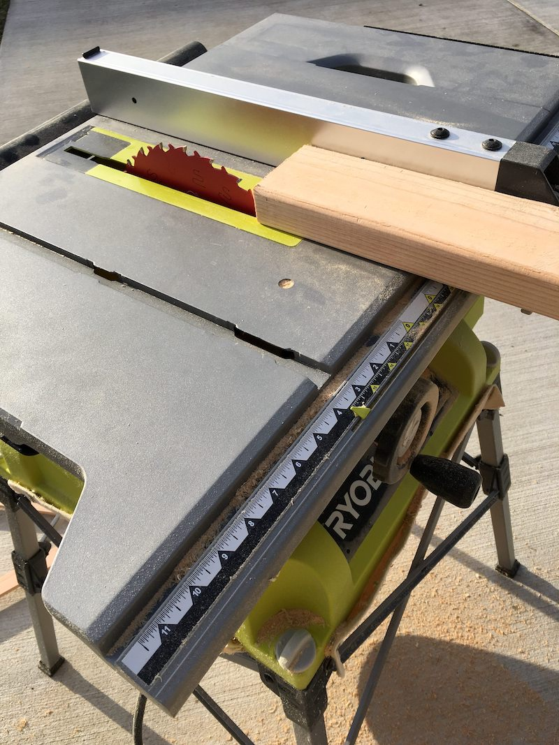 Cutting a wood board with a Ryobi table saw