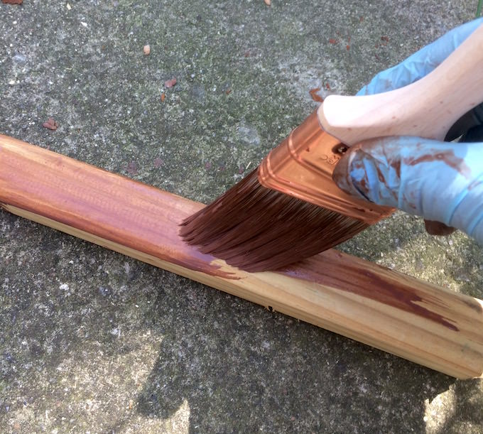Staining 2 x 2s with a brush wearing gloves