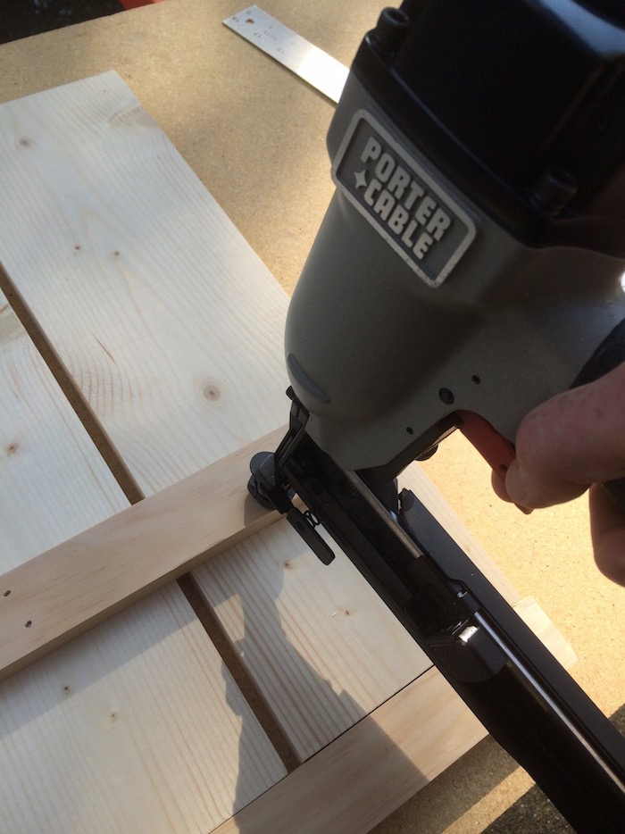 Staple gun attaching two pieces of wood