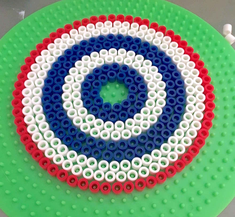 Perler bead drink cover laid out on a pegboard
