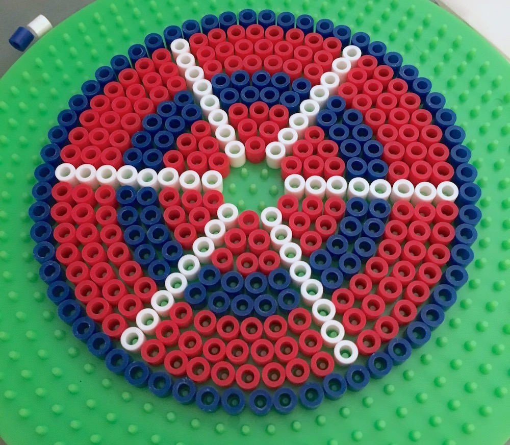 Red white and blue perler beads on a round pegboard