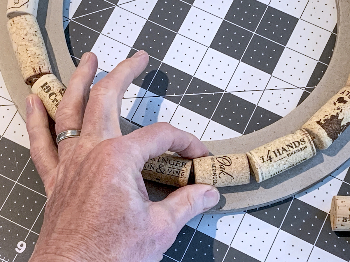Hand gluing corks around a wreath ring