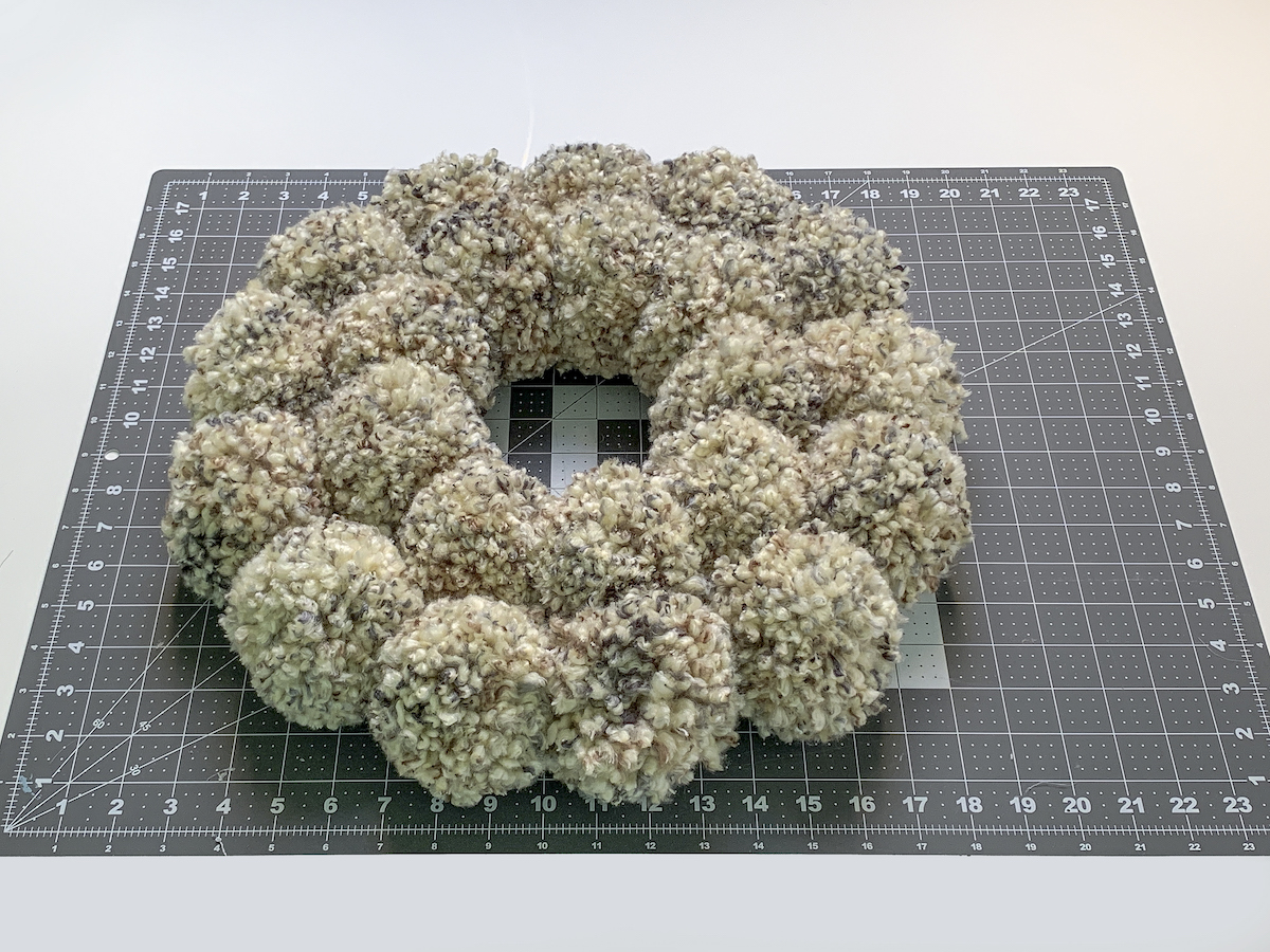 Finished pom pom wreath laying on a craft mat