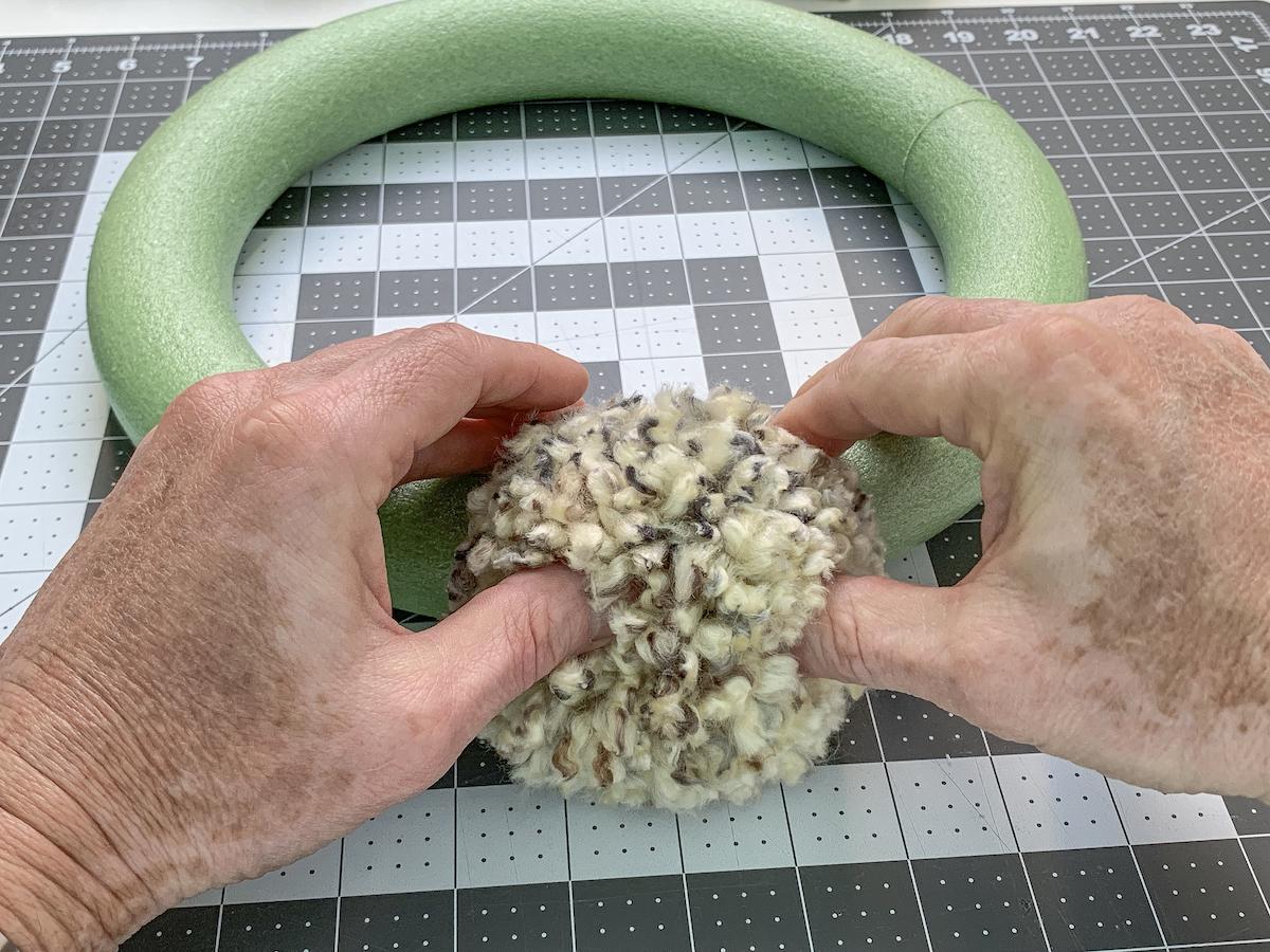 Pressing a pom pom onto a wreath form