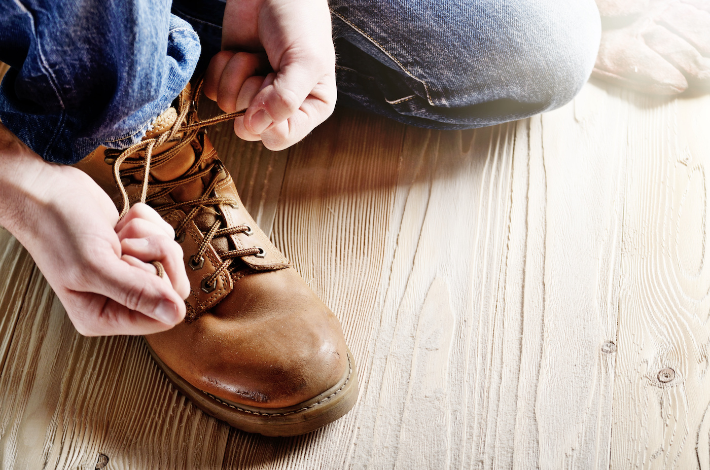 Carpenter in blue jeans tying shoelaces of yellow work boots on on wooden floor