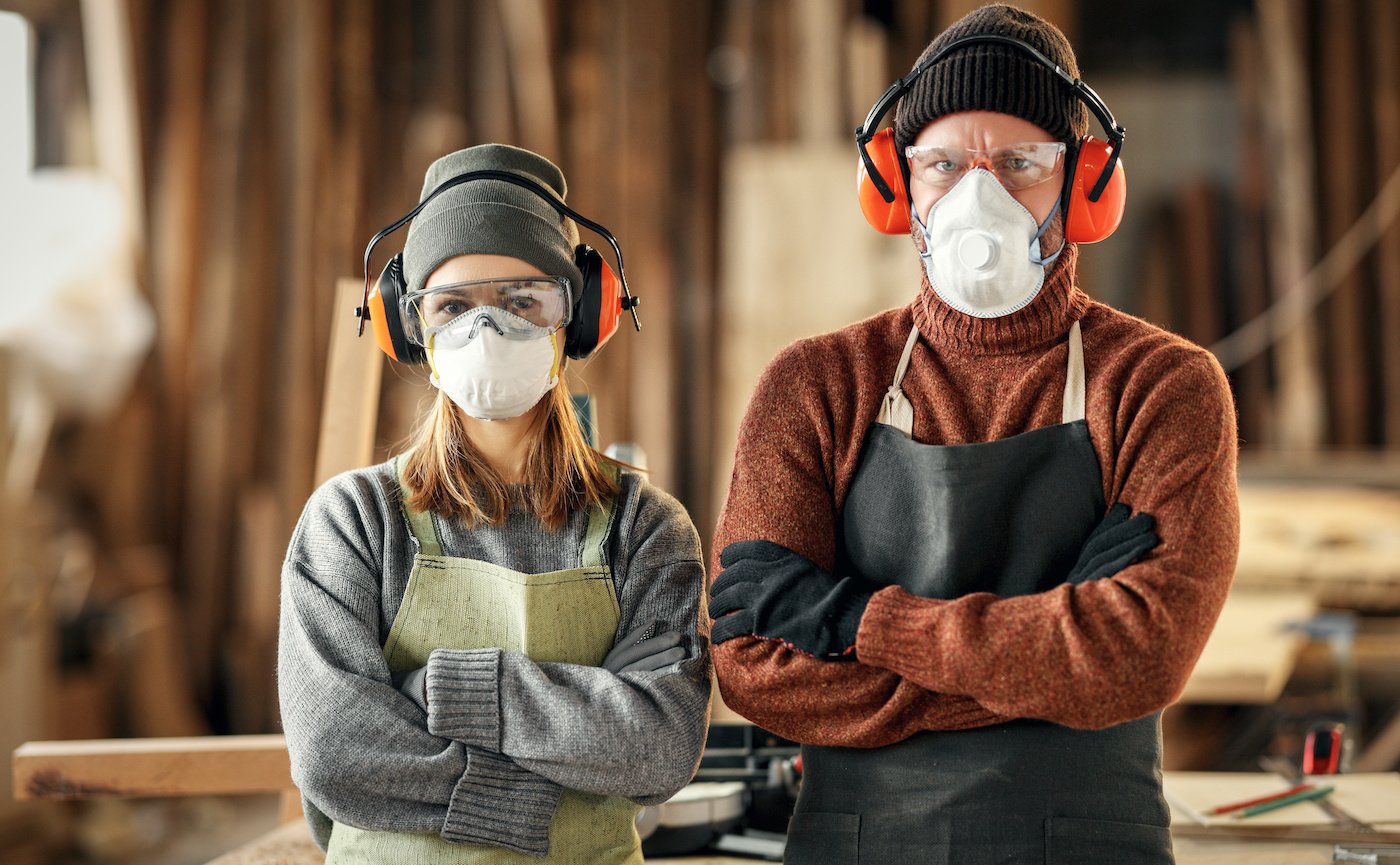 Couple of professional carpenters in respirators and protective goggles and headphones looking at camera while standing together in workshop