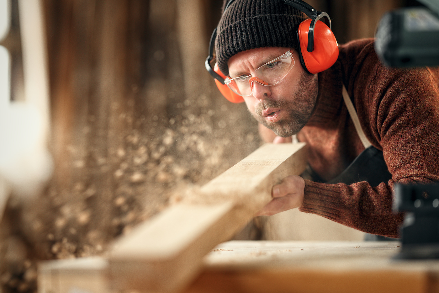 Adult male woodworker in protective goggles and headphones blowing sawdust from wooden detail while working in carpentry workshop