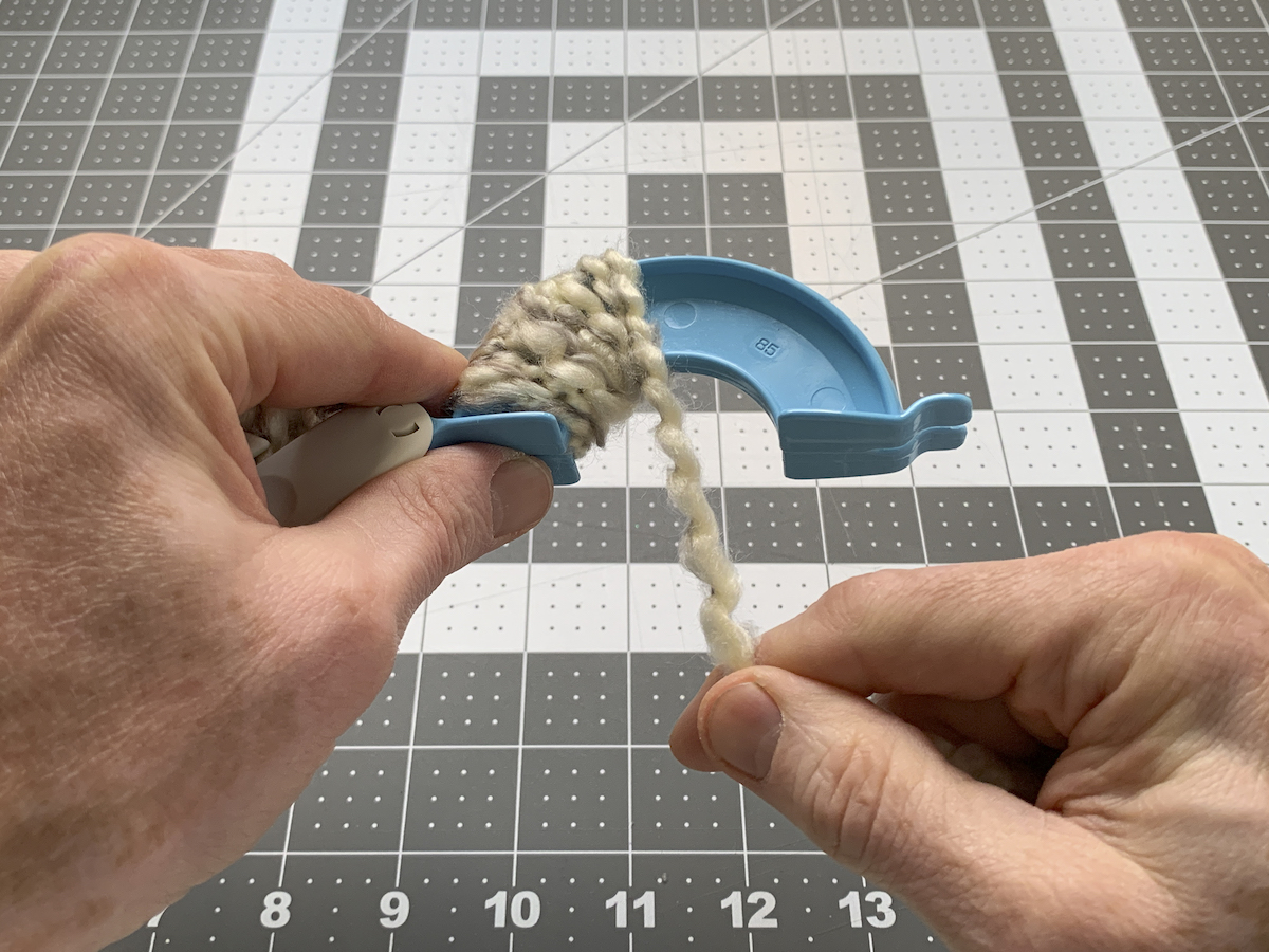 Wrapping yarn on the other side of the pom pom maker