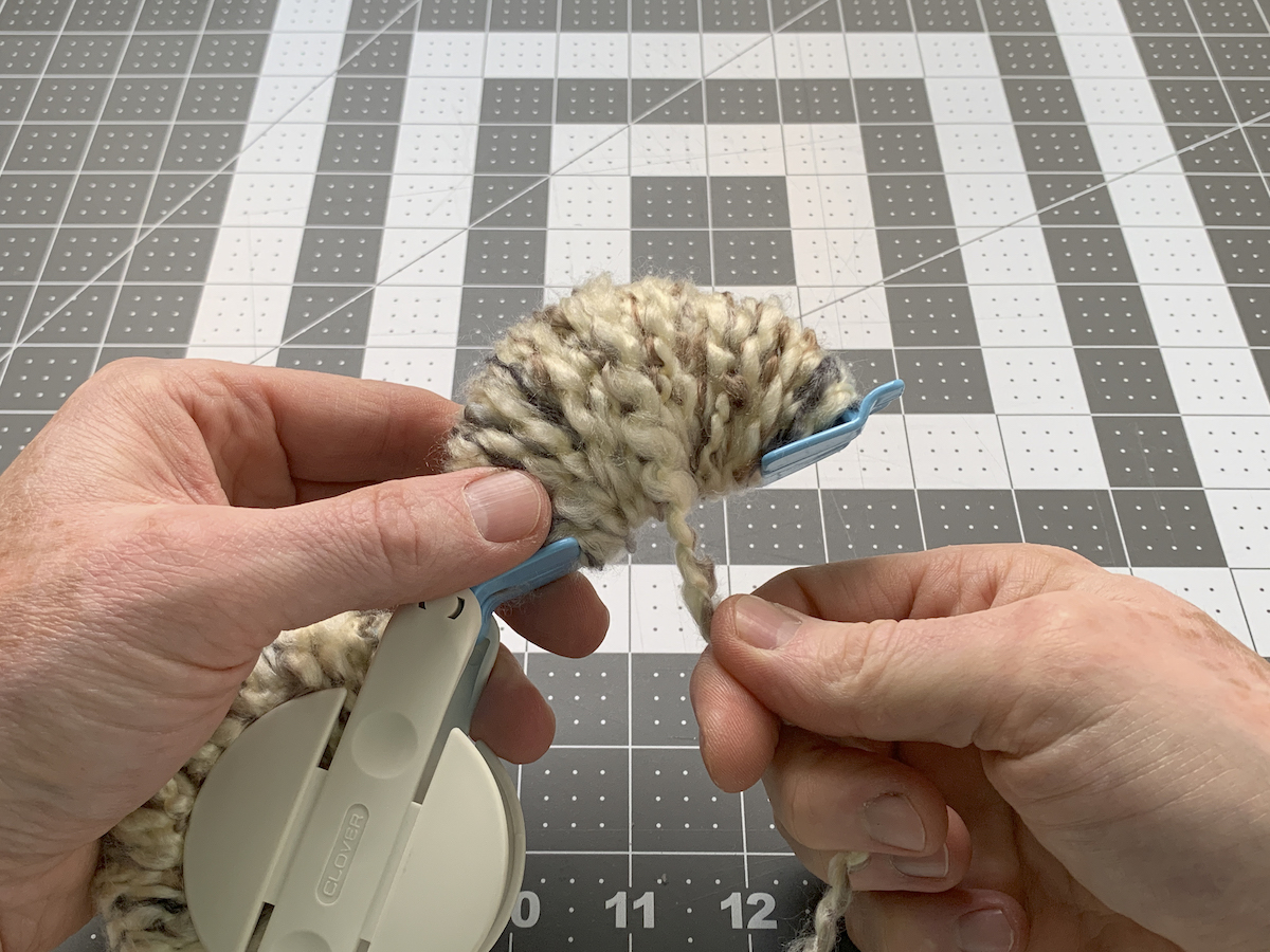 Wrapping yarn thickly around the pom pom maker
