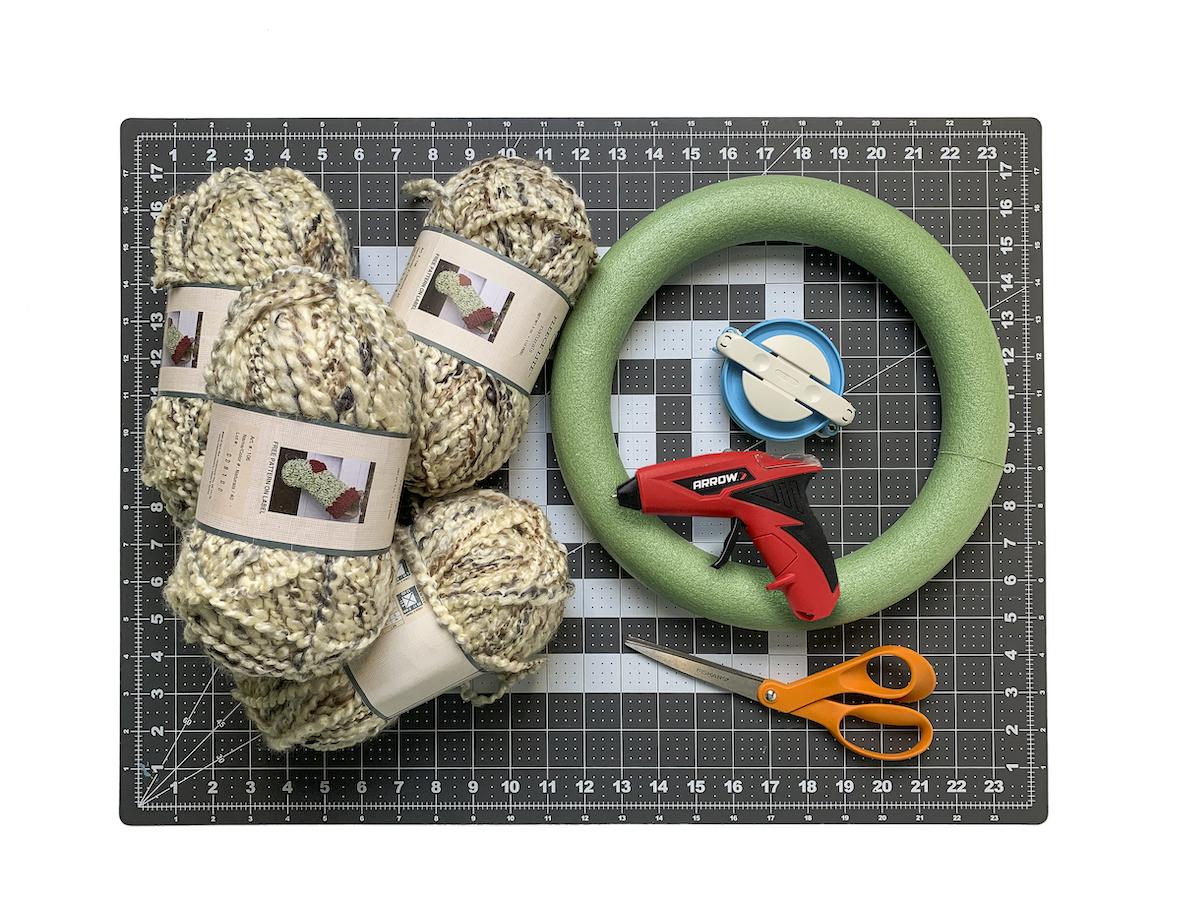 Yarn wreath form pom pom maker and hot glue gun laying on a cutting mat