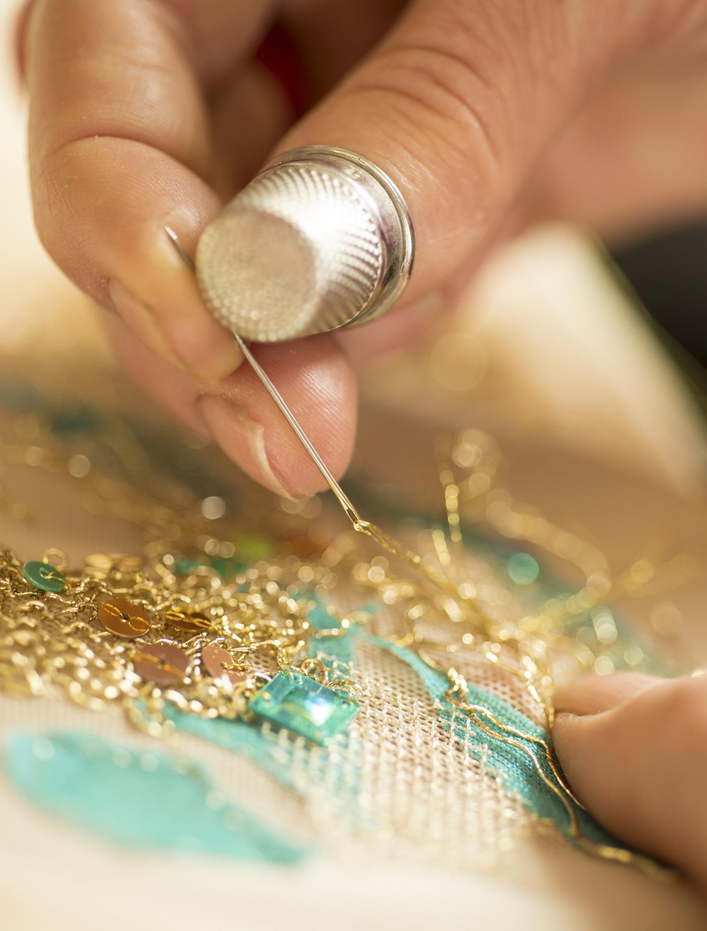 Mãos e dedal fazendo bordado com fio dourado