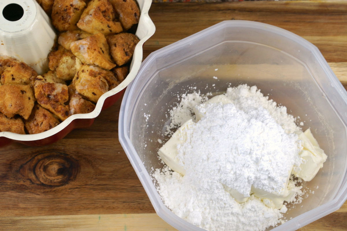 Baked pumpkin monkey bread next to a container filled with butter and powdered sugar