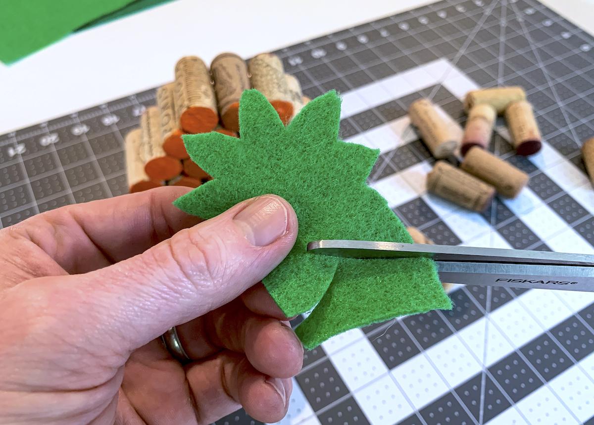 Cutting pumpkin stems out of green felt iwth scissors