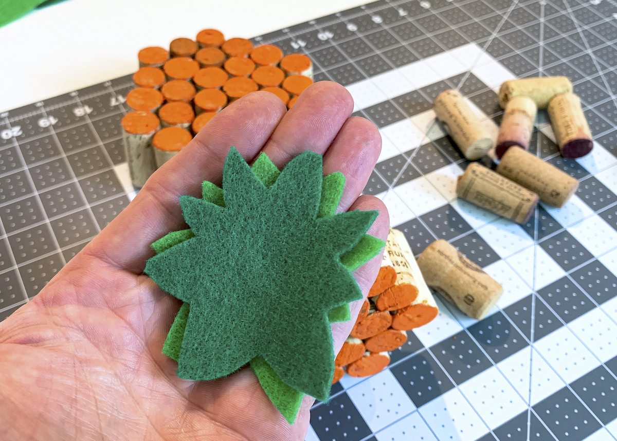 Green felt stems cut out and sitting in a man's hand