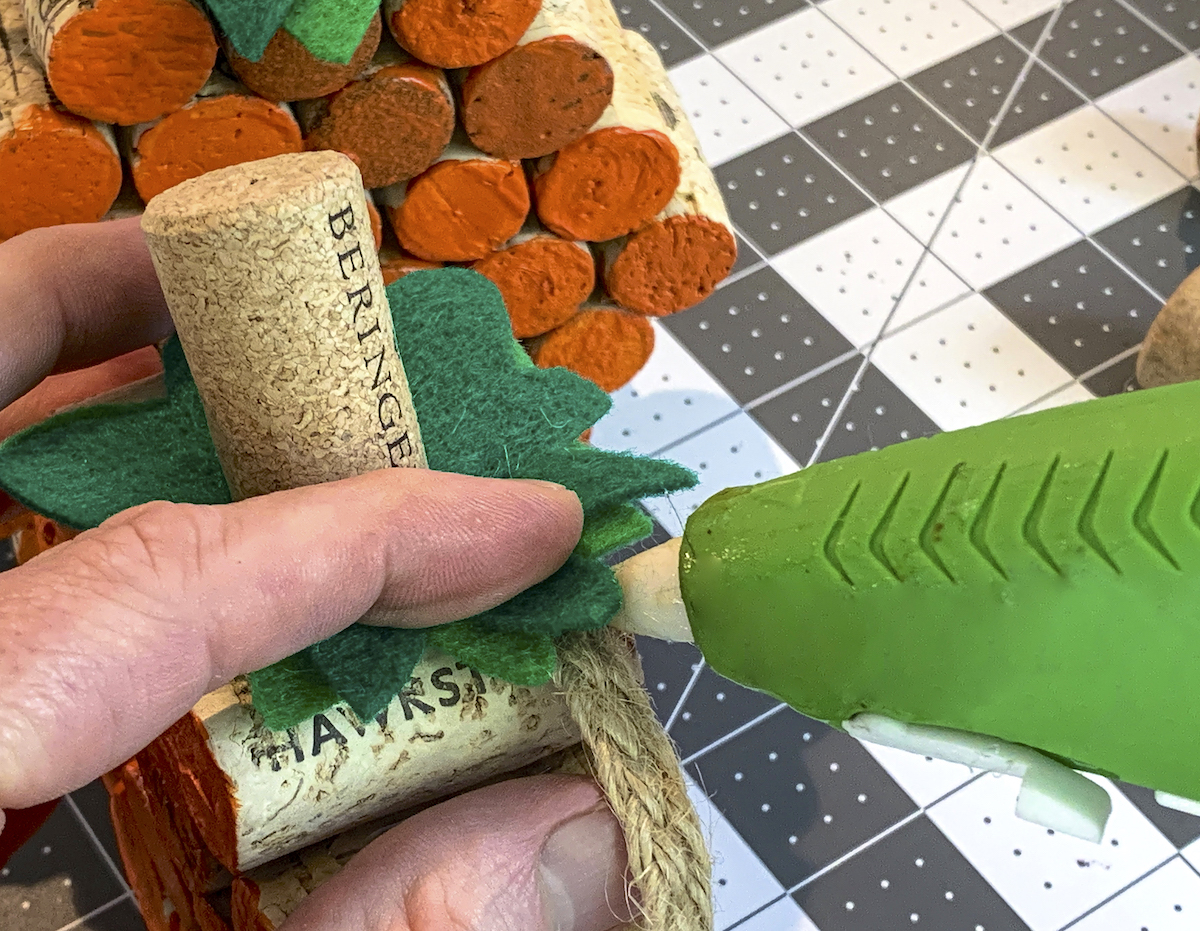 Hot gluing burlap ribbon underneath green felt stems