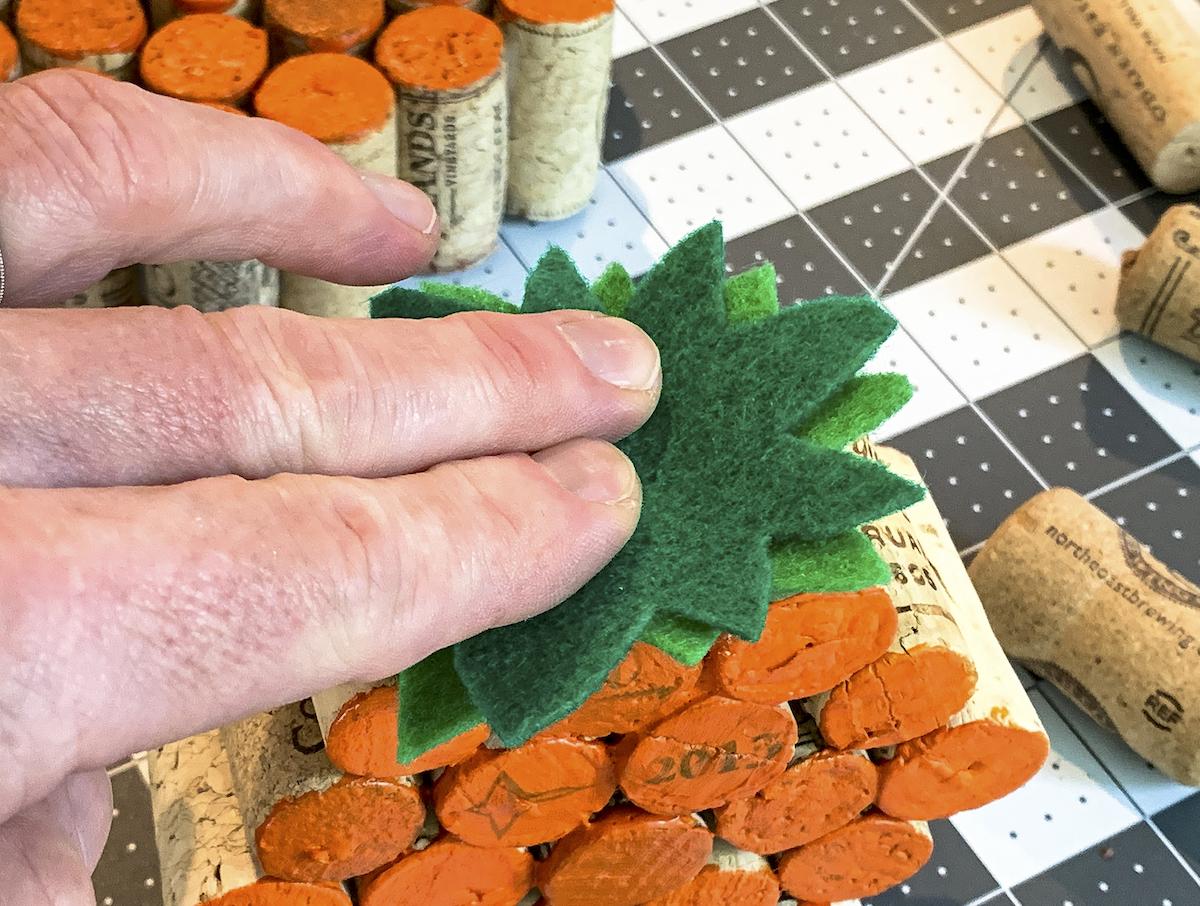 Hot gluing green felt stems to the top of a wine cork pumpkin
