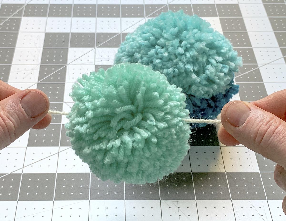 Pom pom strung onto a piece of yarn to make a garland