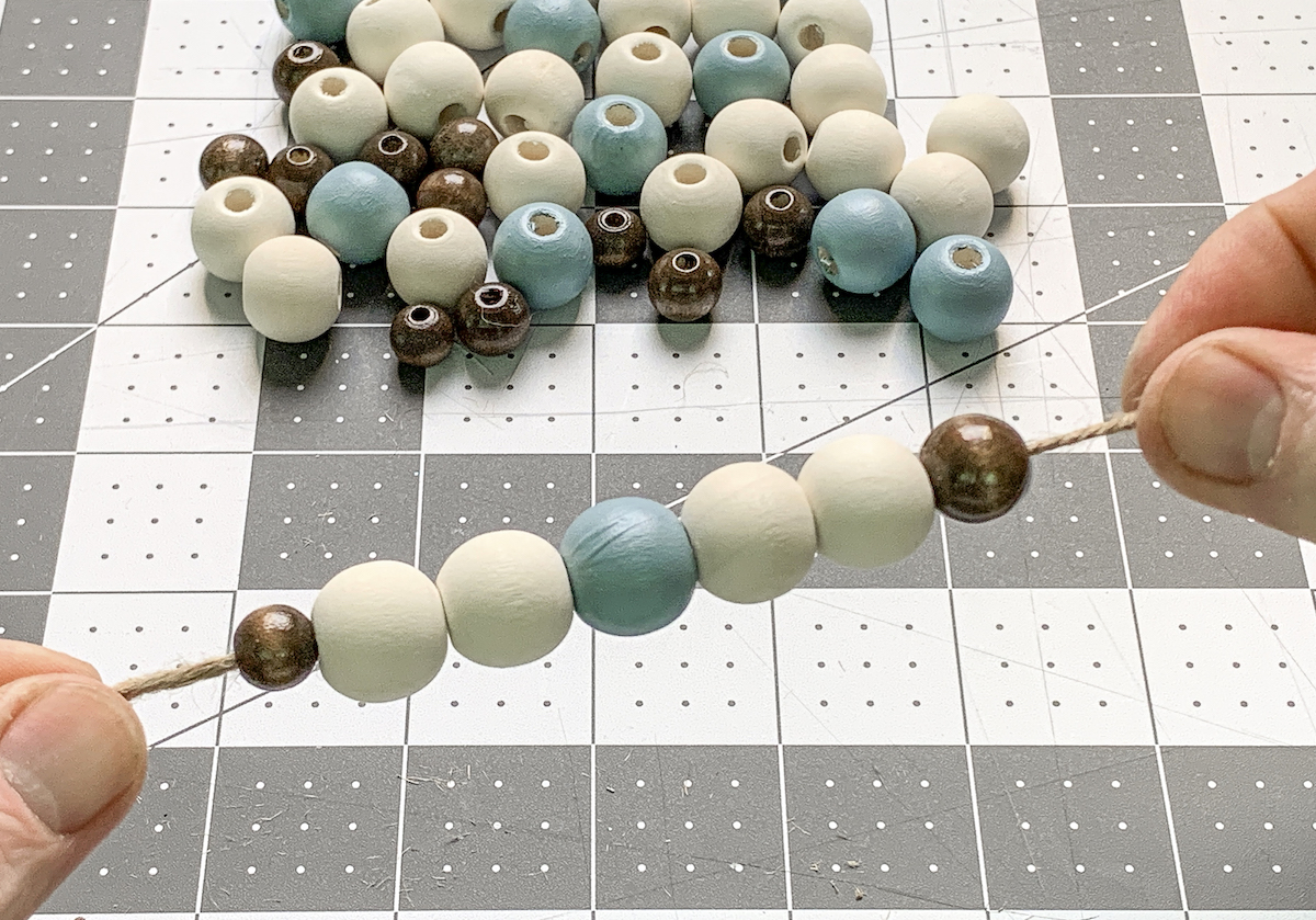 Stringing wood beads onto jute twine
