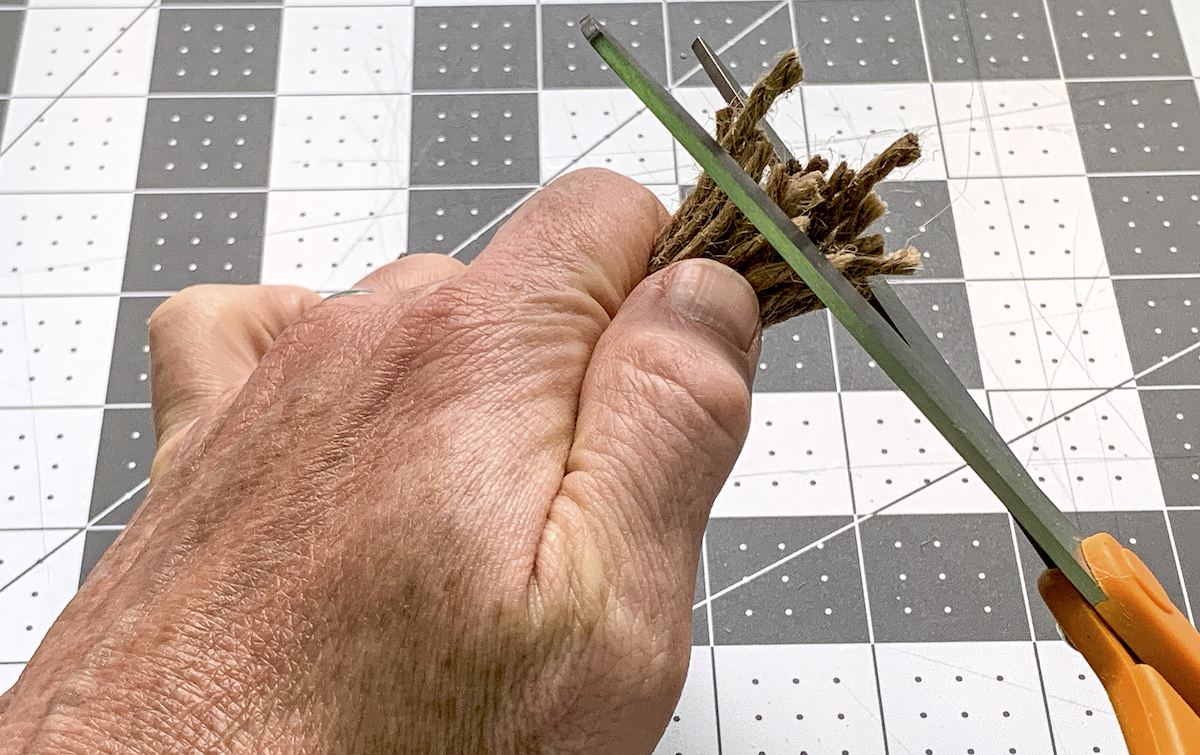 Trimming the end of a jute tassel with scissors